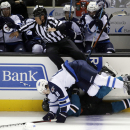 Winnipeg Jets defenseman Jacob Trouba (8) collides against the boards with San Jose Sharks center Logan Couture, bottom, and line referee Jay Sharrers, top, during the first period of an NHL hockey game Saturday, Oct. 11, 2014, in San Jose, Calif The Ass
