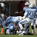 Tennessee Titans safety Bernard Pollard, top center, dives on top of safety Michael Griffin, bottom left, as Griffin scuffles with Justin Hunter, bottom right, after a play during NFL football training camp Tuesday, July 29, 2014, in Nashville, Tenn The A