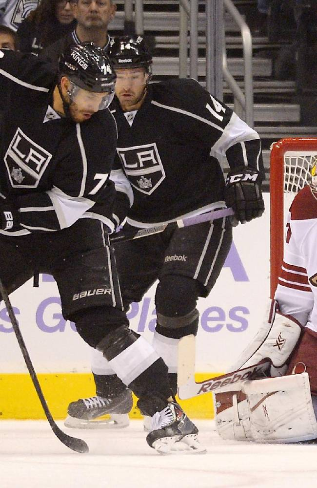 Los Angeles Kings center Dwight King, left, deflects a shot between the legs of Phoenix Coyotes goalie Mike Smith, right, for a goal as right wing Justin Williams looks on during the first period of their NHL hockey game, Thursday, Oct. 24, 2013, in Los Angeles