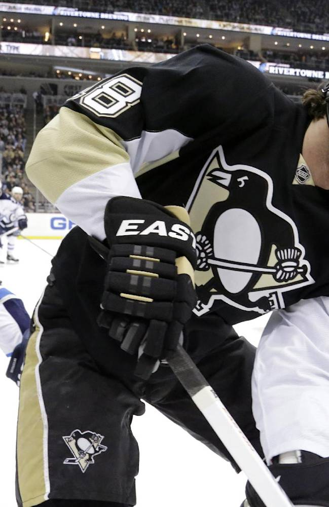 Pittsburgh Penguins' James Neal, right, works the puck in the corner during the second period of an NHL hockey game against the Winnipeg Jets in Pittsburgh, Sunday, Jan. 5, 2014