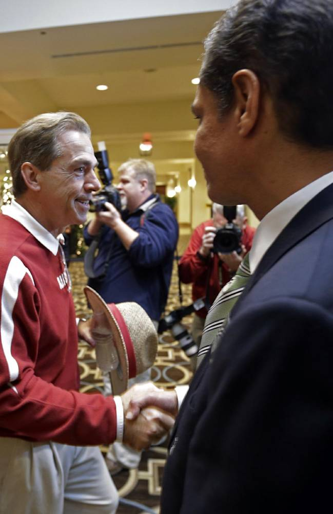 Alabama coach Nick Saban is greeted by Sugar Bowl Committee members as he arrives with the team at a hotel after practice in New Orleans, Friday, Dec. 27, 2013. Alabama will play Oklahoma in the Sugar Bowl NCAA college football game on Jan. 2