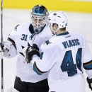 San Jose Sharks goalie Antti Niemi, left, from Finland, is congratulated by Marc-Edouard Vlasic after a 3-2 win over the Calgary Flames following an NHL hockey game in Calgary, Alberta, Saturday Dec. 6, 2014 The Associated Press