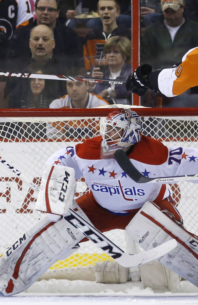 Philadelphia Flyers' Vincent Lecavalier, right, tries to knock the puck past Washington Capitals' Braden Holtby during the first period of an NHL hockey game, Wednesday, March 5, 2014, in Philadelphia