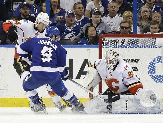 Calgary Flames goalie Karri Ramo (31), of Finland, makes a save on a shot by Tampa Bay Lightning center Tyler Johnson (9) during the first period of an NHL hockey game on Thursday, April 3, 2014, in Tampa, Fla. Flames' Chris Butler (44) also defends