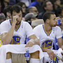 Golden State Warriors center Andrew Bogut, left, and guard Stephen Curry, right, rest on the bench during the third quarter of their NBA basketball game against the San Antonio Spurs Saturday, March 22, 2014, in Oakland, Calif. San Antonio won the game 99