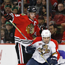 Chicago Blackhawks center Jonathan Toews, left, and Florida Panthers defenseman Mike Weaver (43) battle during the second period of an NHL hockey game on Sunday, Dec. 8, 2013, in Chicago, Ill The Associated Press