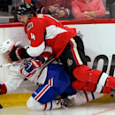 Ottawa Senators' Chris Phillips hits Montreal Canadiens' Christian Thomas to the ice during the second period of a preseason NHL hockey game in Ottawa, Ontario, on Friday, Oct. 3, 2014 The Associated Press