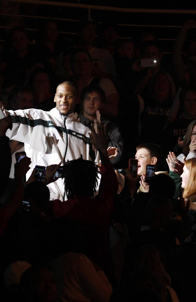 Michigan State's Adreian Payne greets fans as he is introduced before an NCAA college basketball scrimmage, Friday, Oct. 18, 2013, in East Lansing, Mich
