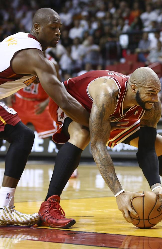 Miami Heat's Dwyane Wade (3) reaches for the ball held by Chicago Bulls' Carlos Boozer during the second half of a NBA basketball game in Miami, Tuesday, Oct. 29, 2013. The Heat won 107-95