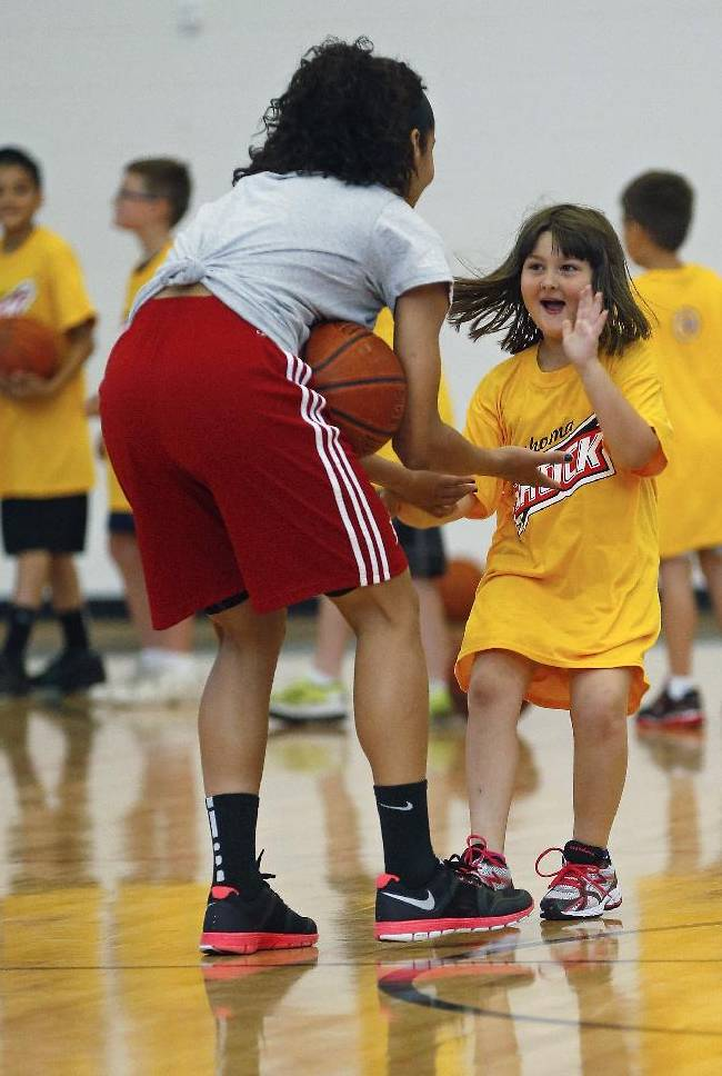 Seven-year-old Haleigh Legg, right, runs to slap hands with Skylar Diggins, left, of the WNBA Tulsa Shock, during a basketball clinic for Moore students impacted by the tornado, in Moore, Okla., Monday, June 17, 2013. Legg was a student at Plaza Towers Elementary School