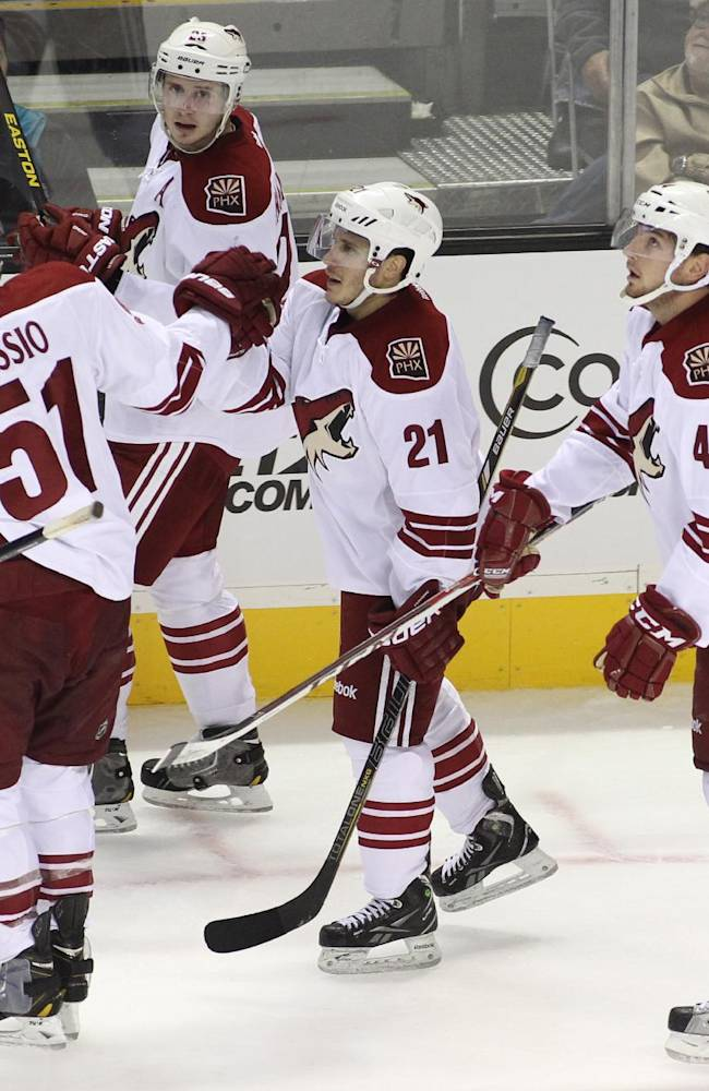 The Coyotes' Andy Miele (21) is congratulated by teammates for his second period goal against the Sharks during an NHL preseason hockey game in San Jose, Calif., Saturday, Sept. 21, 2013
