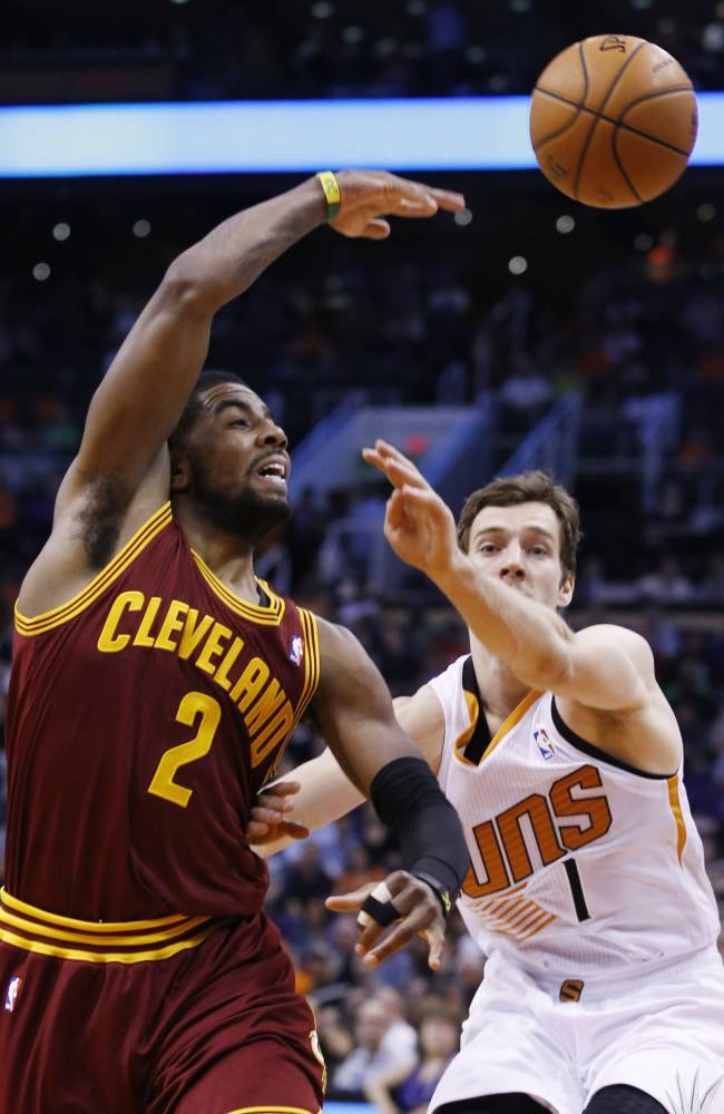 Cleveland Cavaliers' Kyrie Irving (2) gets off a pass over Phoenix Suns' Goran Dragic (1), of Slovenia, during the first half of an NBA basketball game on Wednesday, March 12, 2014, in Phoenix