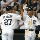 Detroit Tigers runner Jhonny Peralta (27) celebrates with Quintin Berry while scoring on a single by teammate Austin Jackson during the seventh inning of a baseball game against the Chicago White Sox in Detroit, Friday, July 20, 2012. (AP Photo/Carlos Osorio)