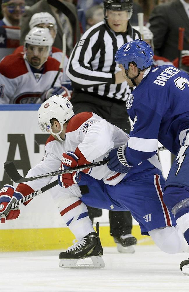 Tampa Bay Lightning defenseman Eric Brewer (2) takes down Montreal Canadiens left wing Thomas Vanek (20), of Austria, as they go for a loose puck during the for period of Game 2 of a first-round NHL hockey playoff series on Friday, April 18, 2014, in Tampa, Fla