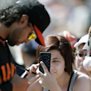 San Francisco Giants fan Terra Curiel, right, takes a picture of San Francisco Giants center fielder Angel Pagan, left, as he signs autographs before playing the Colorado Rockies in an exhibition spring training baseball game Tuesday, March 4, 2014, in Sc