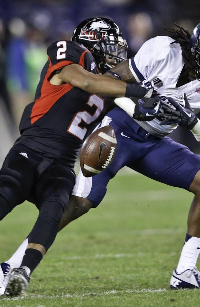 Northern Illinois cornerback Sean Evans strips away the ball from Utah State receiver Ronald Butler after a catch during the first half of the Poinsettia Bowl NCAA college football game Thursday, Dec. 26, 2013, in San Diego. Utah State recovered the fumble