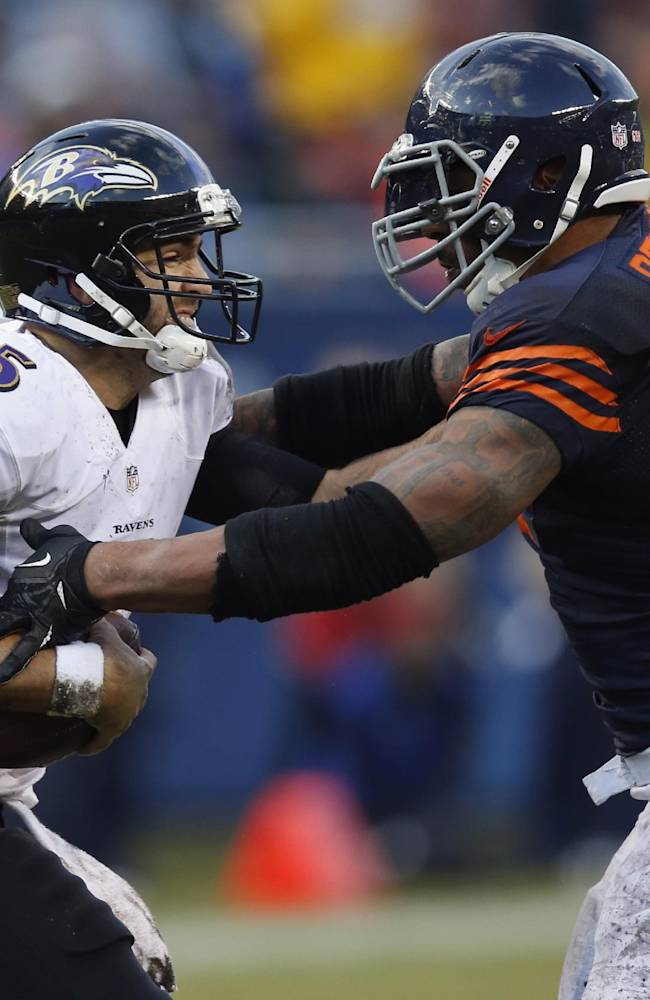 Baltimore Ravens quarterback Joe Flacco (5) pushes off Chicago Bears defensive end Julius Peppers (90) during the first half of an NFL football game, Sunday, Nov. 17, 2013, in Chicago