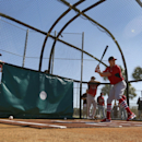 St. Louis Cardinals' Peter Bourjos, right, takes batting practice as hitting coach John Mabry, left, watches during spring training baseball practice Sunday, Feb. 16, 2014, in Jupiter, Fla The Associated Press