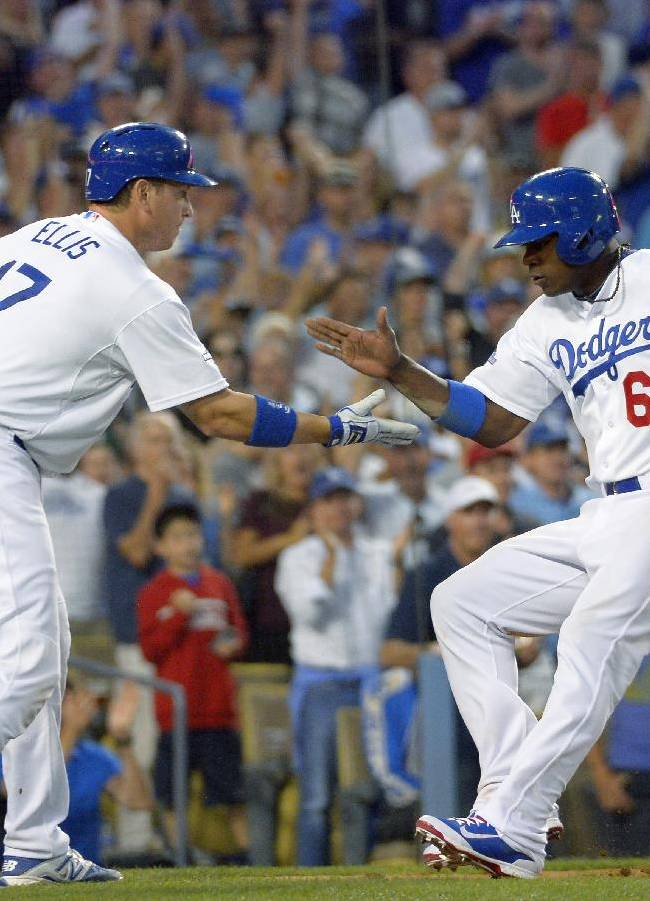 Los Angeles Dodgers' Yasiel Puig (66), is greeted by teammate A.J. Ellis, left, after Puig scored on a single by hit by Dodgers' Skip Schumaker in the third inning in Game 3 of the National League division baseball series against the Atlanta Braves, Sunday, Oct. 6, 2013, in Los Angeles
