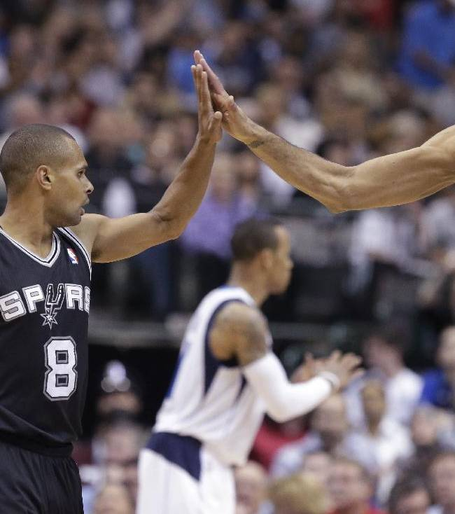 San Antonio Spurs guard Patty Mills (8) receives congratulations from Tim Duncan (21) during the second half an NBA basketball game against the Dallas Mavericks on Thursday, April 10, 2014, in Dallas. The Spurs won 109-100
