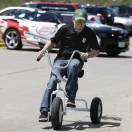 NASCAR driver Justin Allgaier rides a tricycle during a promotion for the DuPont Pioneer 250 NASCAR Nationwide Series auto race to be held in June at the Iowa Speedway, Monday, May 20, 2013, in Des Moines, Iowa. Allgaier is 4th in the Nationwide standings even though a win has eluded him so far in 2013. (AP Photo/Charlie Neibergall)