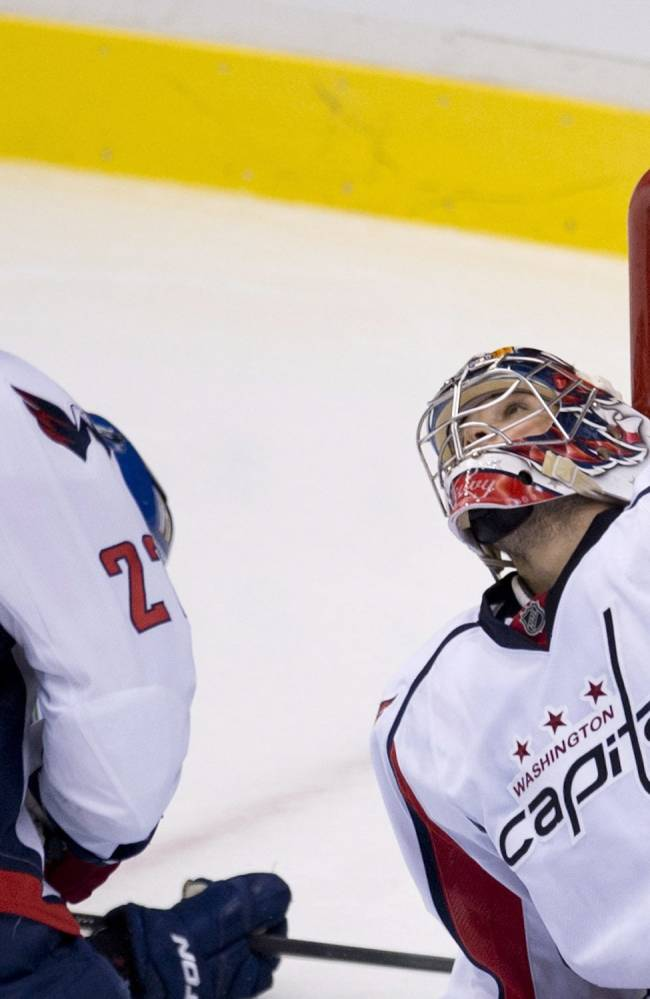 Washington Capitals defenceman Karl Alzner (27) and Capitals goalie Michal Neuvirth (30) stop a shot from the Vancouver Canucks during the second period of NHL hockey action in Vancouver, British Columbia on Monday, Oct. 28, 2013