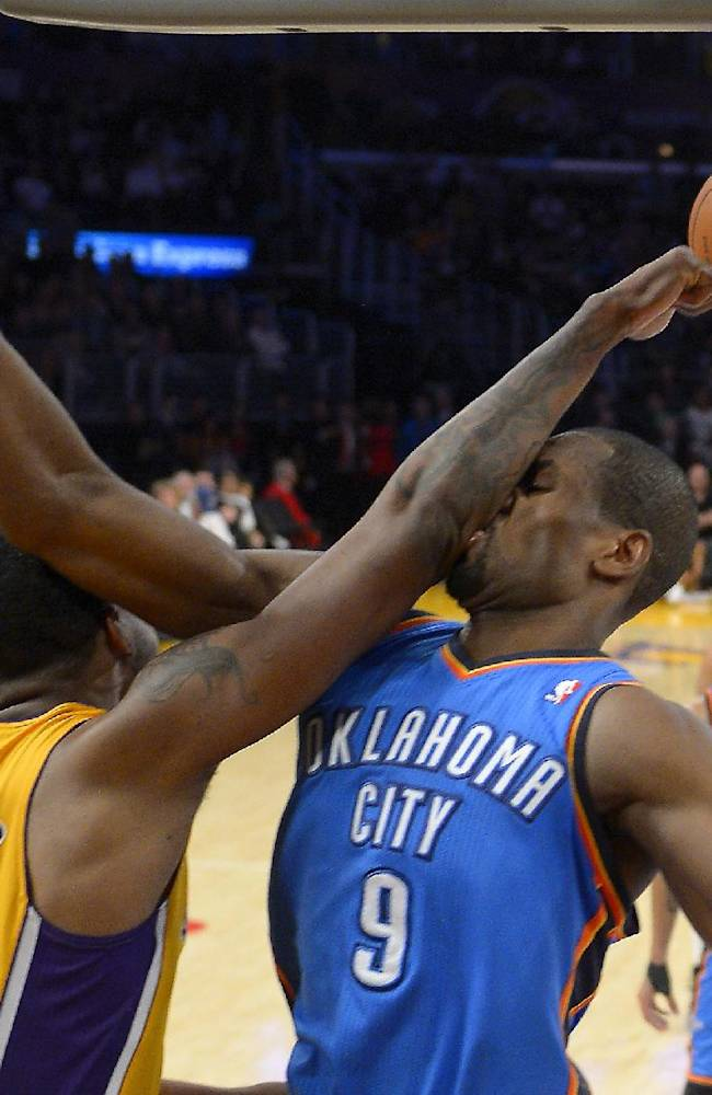 Oklahoma City Thunder power forward Serge Ibaka, right, of Congo, is hit in the face after rejecting the shot of Los Angeles Lakers power forward Shawne Williams, left, during the second half of an NBA basketball game, Thursday, Feb. 13, 2014, in Los Angeles