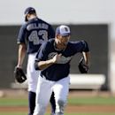 San Diego Padres' Josh Johnson, front, sprints to cover first in fielding practice as Joe Wieland (43) stands on the mound during spring training baseball practice, Sunday, Feb. 16, 2014, in Peoria, Ariz The Associated Press