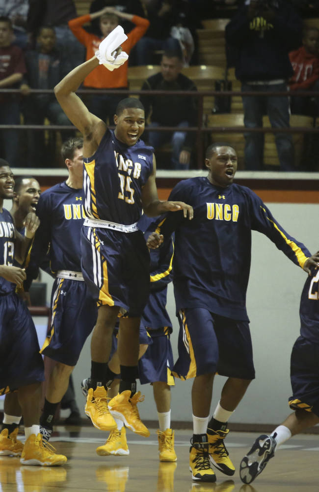 UNC-Greensboro's Madestas Masilionis (15) and teammates celebrate after they defeated Virginia Tech 55-52 in an NCAA college basketball game in Blacksburg, Va., Saturday, Dec. 28 2013