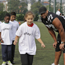 Oakland Raiders Austin Howard trains children during an event at Guildford, England, Tuesday, Sept. 23, 2014. The Raiders will play the Miami Dolphins in an NFL football game at London's Wembley Stadium on Sunday Sept. 28. The Associated Press