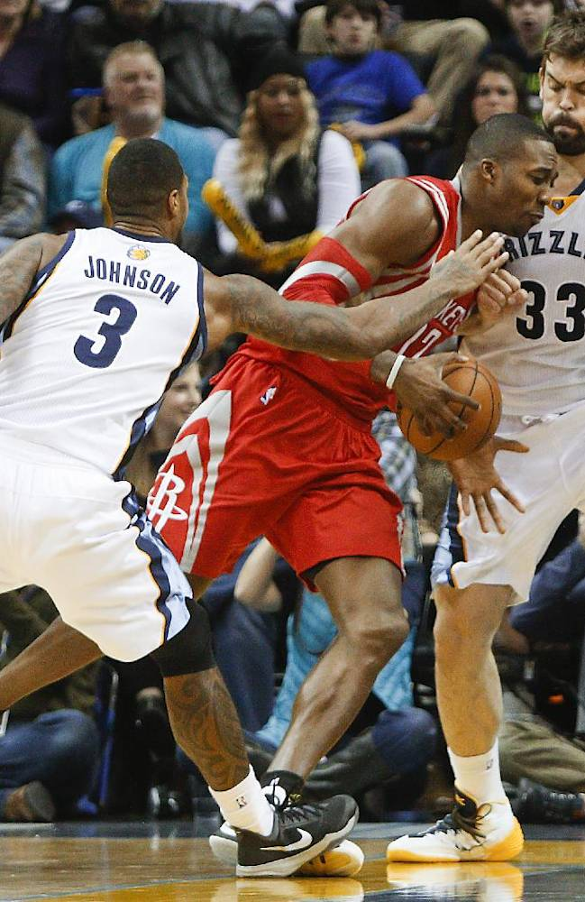Houston Rockets center Dwight Howard (12) drives to the basket against Memphis Grizzlies forward James Johnson (3) and center Marc Gasol (33) in the second half of an NBA basketball game Saturday, Jan. 25, 2014, in Memphis, Tenn. The Grizzlies won 99-81