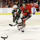 Minnesota Wild's Torrey Mitchell (17) controls the puck against Chicago Blackhawks' Andrew Shaw (65) during the second period