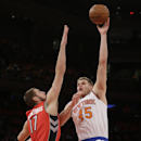 New York Knicks' Cole Aldrich (45) shoots over Toronto Raptors' Jonas Valanciunas (17) during the first half of an NBA basketball game Wednesday, April 16, 2014, in New York The Associated Press