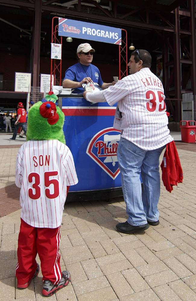 A father buys his son a program for an opening day baseball game between the Milwaukee Brewers and Philadelphia Phillies in Philadelphia, Tuesday, April 8, 2014