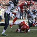 Kansas City Chiefs running back Knile Davis (34) scores a touchdown against the Seattle Seahawks as Seattle Seahawks cornerback Richard Sherman, left, and Kansas City Chiefs wide receiver Frankie Hammond, top center, look on, in the second half of an NFL