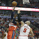 Washington Wizards guard John Wall, left, shoots over Chicago Bulls forward Carlos Boozer during the first half in Game 1 of an opening-round NBA basketball playoff series in Chicago, Sunday, April 20, 2014 The Associated Press