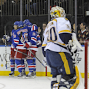 New York Rangers celebrate with Rick Nash after Nash scored as Nashville Predators goaltender Carter Hutton reacts during the second period of an NHL hockey game Tuesday, Dec. 10, 2013, at Madison Square Garden in New York. The Predators defeated the Ran