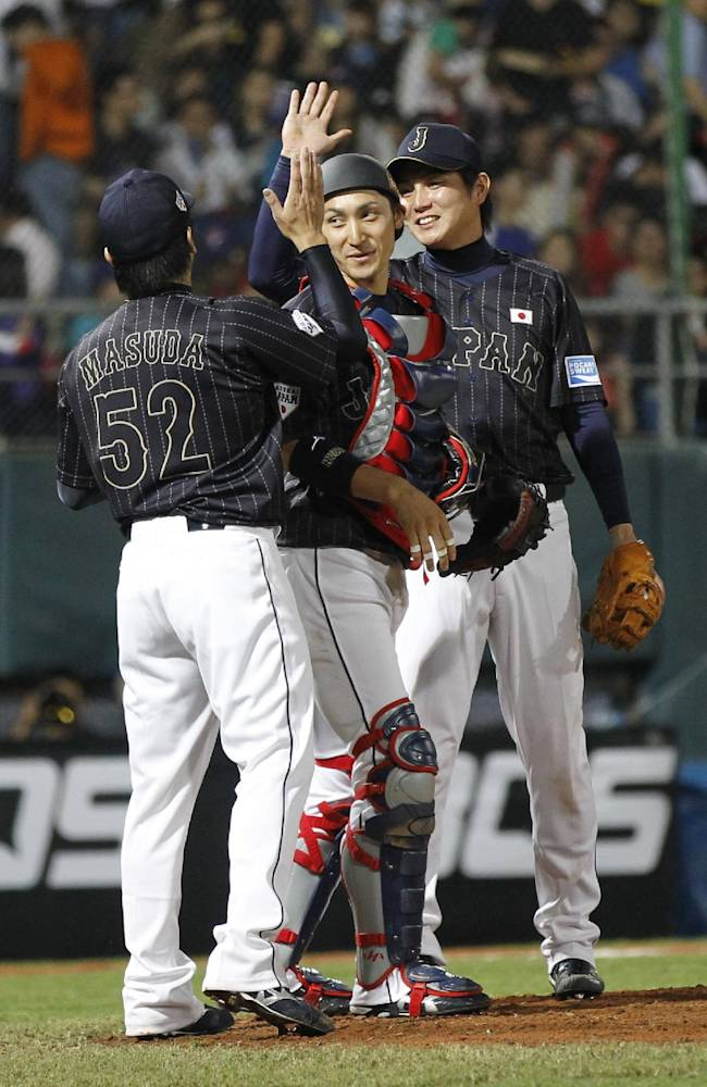 Japan's Shingo Kawabata, right, claps hands with pitcher Naoya Masuda, front, over catcher Hikaru Itoh after beating Taiwan 4-2 during an exhibition game at the Xinzhuang baseball stadium in New Taipei City, Taiwan, Friday, Nov. 8, 2013