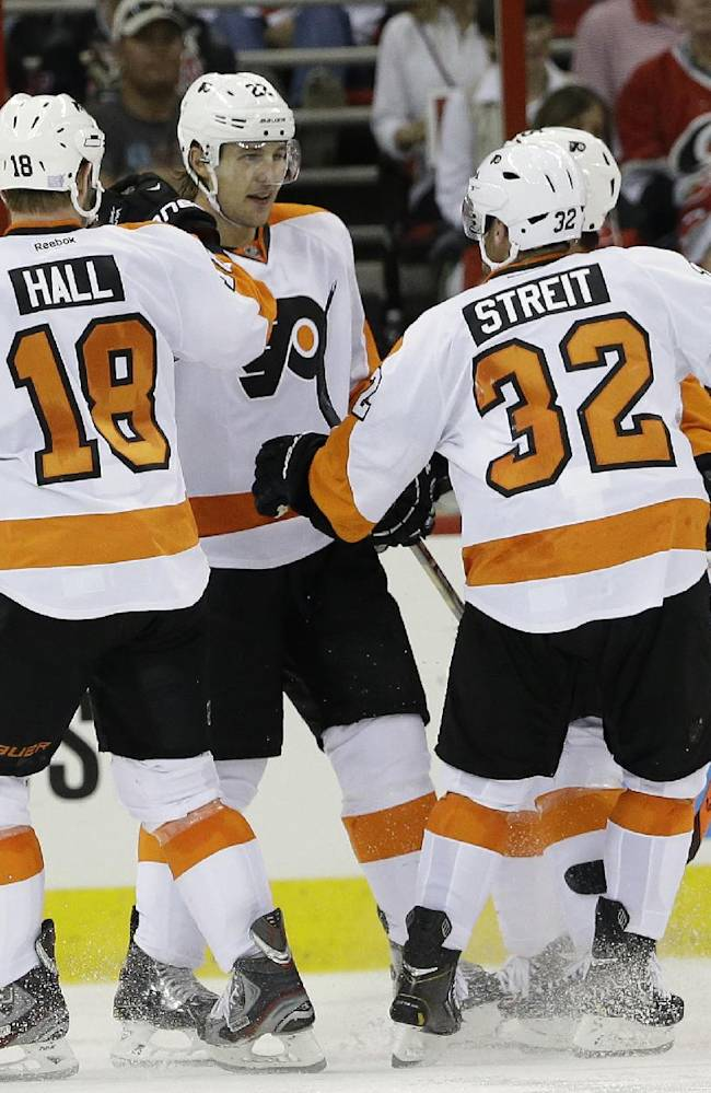 Philadelphia Flyers' Luke Schenn (22) is congratulated by Adam Hall (18) and Mark Streit (32), of Switzerland, following Schenn's goal against the Carolina Hurricanes' during the second period of an NHL hockey game in Raleigh, N.C., Sunday, Oct. 6, 2013