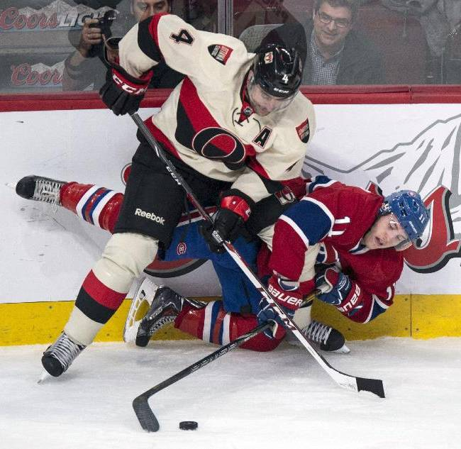 Montreal Canadiens' Brendan Gallagher reaches for the puck as he is overpowered by Ottawa Senators defenseman Chris Phillips, top, during the first period of an NHL hockey game Saturday, March 15, 2014, in Montreal