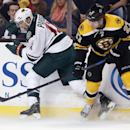 Minnesota Wild left wing Zach Parise (11), of Austria, and Boston Bruins defenseman Dougie Hamilton (27) battle for the puck in the first period of an NHL hockey game in Boston, Tuesday, Oct. 28, 2014 The Associated Press