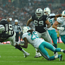 Oakland Raiders' Darren McFadden, left, twists out of a tackle from Miami Dolphins' Louis Delmas during the NFL football game at Wembley Stadium in London, Sunday, Sept. 28, 2014. The Associated Press