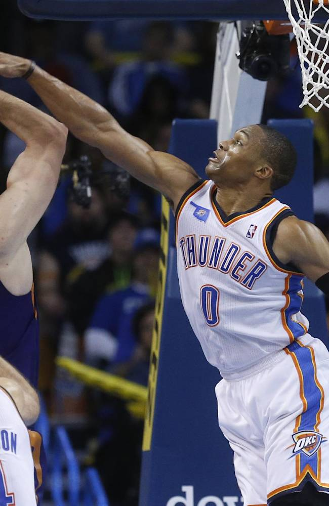 Oklahoma City Thunder guard Russell Westbrook (0) defends on a shot by Phoenix Suns center Miles Plumlee (22) in the fourth quarter of an NBA basketball game in Oklahoma City, Sunday, Nov. 3, 2013. Oklahoma City won 103-96