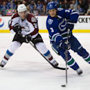 Vancouver Canucks' Kevin Bieksa, right, skates with the puck as Colorado Avalanche's Paul Stastny gives chase during the first period of an NHL hockey game Thursday, April 10, 2014, in Vancouver, British Columbia The Associated Press