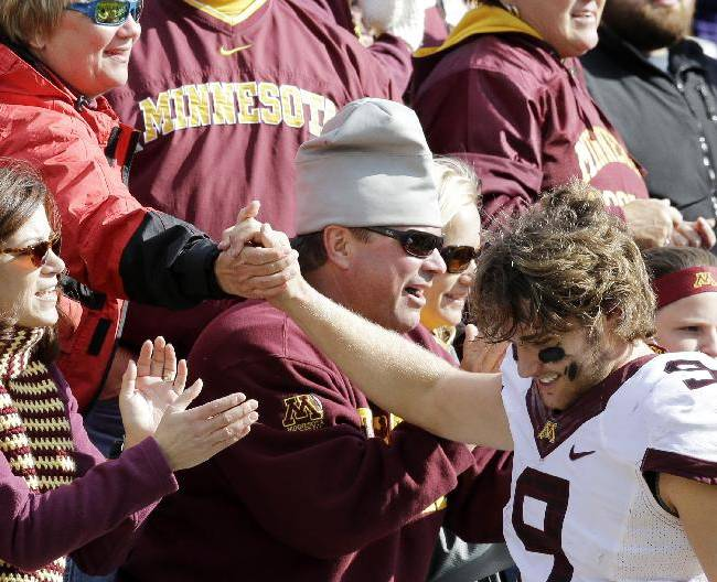 Minnesota quarterback Philip Nelson (9) celebrates with fans after Minnesota defeated Northwestern 20-17 in an NCAA college football game in Evanston, Ill., Saturday, Oct. 19, 2013
