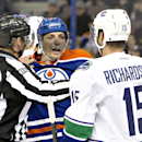 Vancouver Canucks' Brad Richardson (15) and Edmonton Oilers' David Perron (57) are pulled apart by the linesman during first-period NHL hockey game action in Edmonton, Alberta, Friday, Oct. 17, 2014 The Associated Press