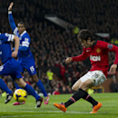 Manchester United's Shinji Kagawa shoots against Everton's goalkeeper Tim Howard, left, during their English Premier League soccer match at Old Trafford Stadium, Manchester, England, Wednesday Dec. 4, 2013