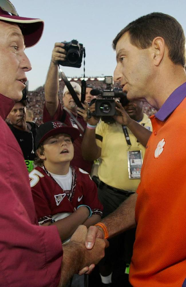 In this Sept. 22, 2012, file photo, Florida State coach Jimbo Fisher, left, shakes hands with Clemson coach Dabo Swinney before the start of an NCAA college football game in Tallahassee, Fla. The two ACC schools meet in what's expected to be a midseason elimination game for the league and national crowns