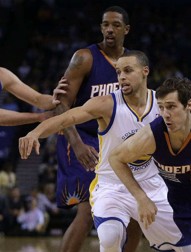 Phoenix Suns' Goran Dragic, right, drives past Golden State Warriors' Stephen Curry, second from right, during the first half of an NBA basketball game Sunday, March 9, 2014, in Oakland, Calif