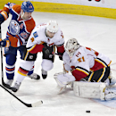 Calgary Flames goalie Karri Ramo (31) makes the save as Kris Russell (4) and Edmonton Oilers' Matt Hendricks (23) looks for a rebound during the third period of an NHL hockey game Saturday, March 22, 2014, in Edmonton, Alberta The Associated Press